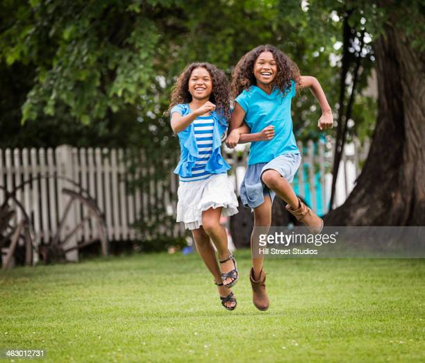 mixed race girls playing in backyard - skipping along stock photos and pictures