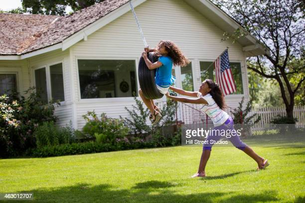 Mixed race girls playing on tire swing