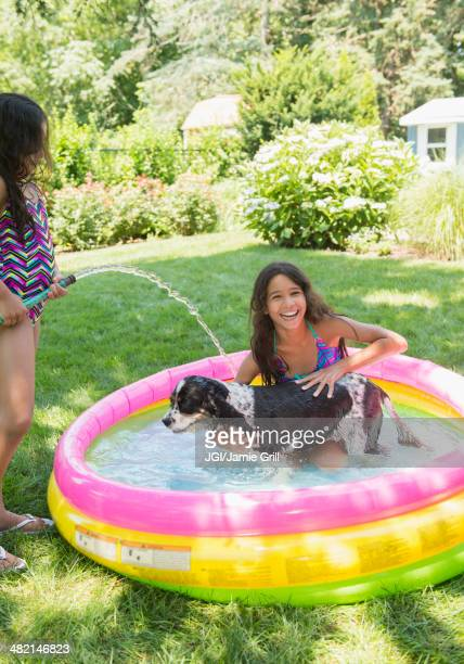 Mixed race girls playing with dog in wading pool