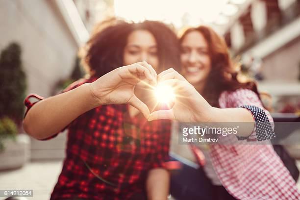 Mixed race girls showing heart shaped hands