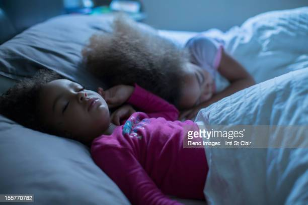 Mixed race girls sleeping in bed