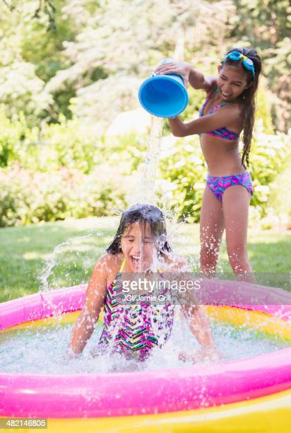 mixed race girls splashing in wading pool - tween girls hot stock photos and pictures