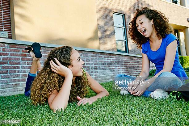 Mixed race girls talking in grass