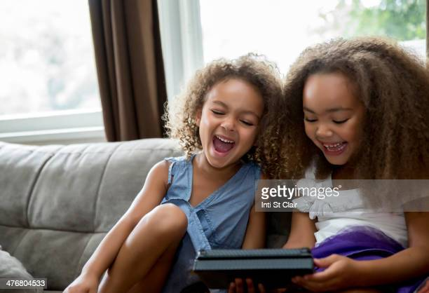 mixed race girls using digital tablet on sofa - free download photo stock photos and pictures
