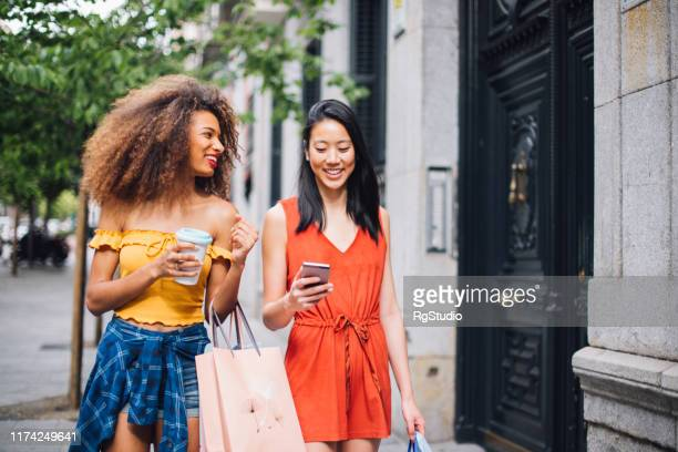 mixed race girls walking with shopping bags - spending money stock pictures, royalty-free photos & images