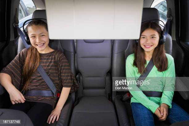 Mixed race girls watching television in backseat