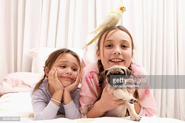 Mixed race girls with dog and bird on bed
