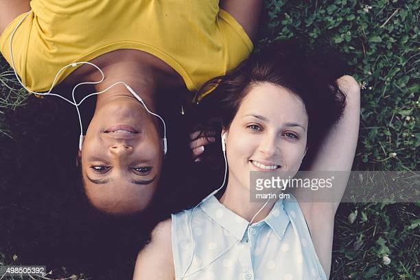 Raza mixta niñas con auriculares en el césped
