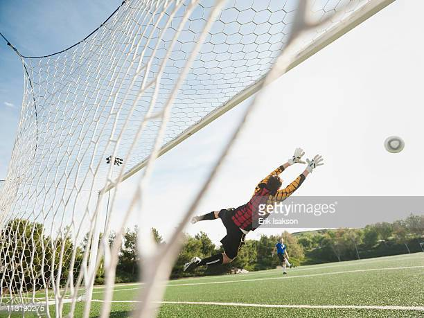 mixed race goalkeeper in mid-air protecting goal - scoring a goal stock pictures, royalty-free photos & images