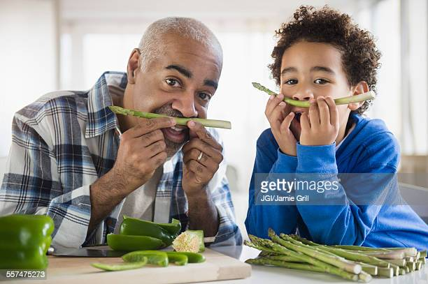 Mixed race grandfather and grandson making mustaches with asparagus