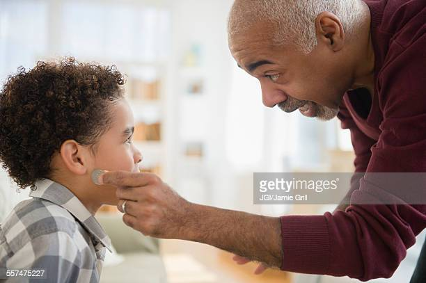 Mixed race grandfather pulling magic coin from ear of grandson