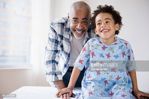 Mixed race grandfather smiling with grandson in hospital
