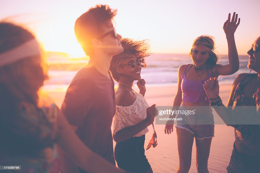 Mixed race group of friends dancing together at a beachparty : Stock Photo