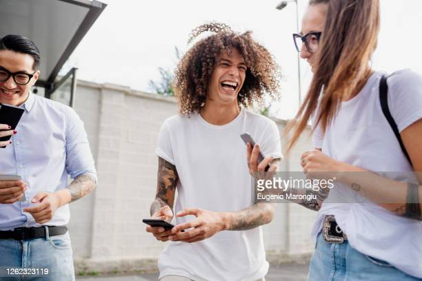 mixed race group of friends hanging out together in town. - photography themes stock pictures, royalty-free photos & images