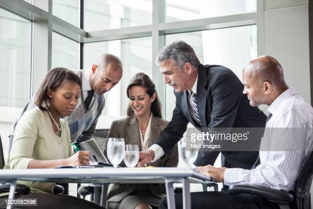 a mixed race group of male and female business people in a meeting at a conference table next to a large window in a convention centre. - 5人 ストックフォトと画像