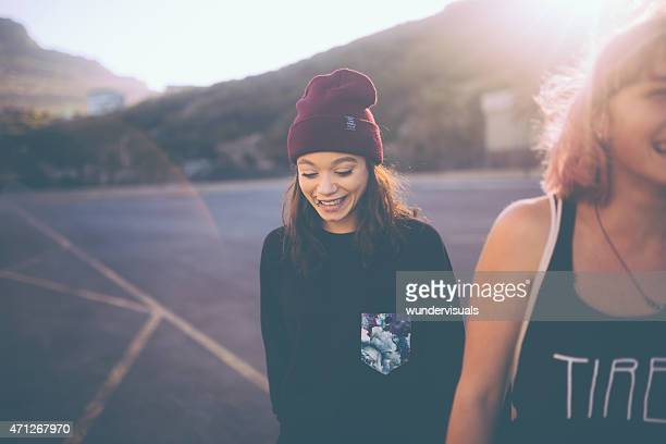 Mixed race grunge girl in beanie walking with a friend