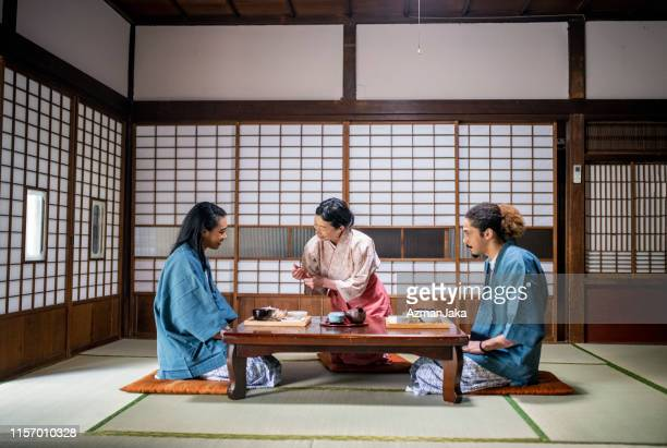 mixed race guests and japanese server at tokyo ryokan - social grace stock pictures, royalty-free photos & images