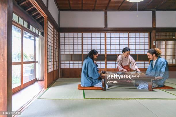 東京旅館のミックスレースゲストと日本のサーバー - 旅館 ストックフォトと画像