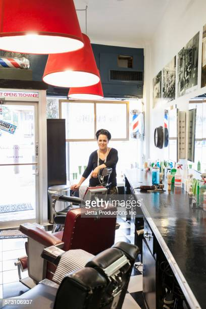 Mixed race hairdresser smiling in retro barbershop