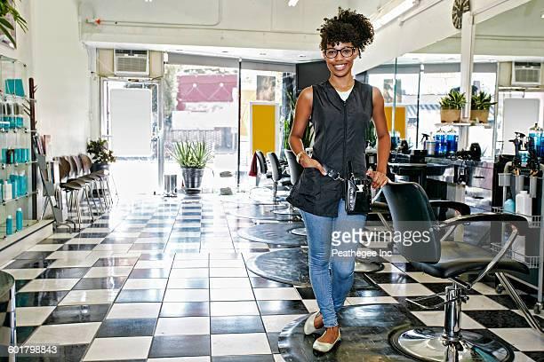 mixed race hairstylist smiling in salon - cabello negro fotografías e imágenes de stock
