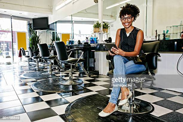 Mixed race hairstylist smiling in salon