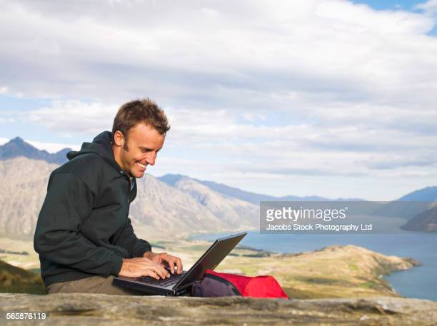 Mixed race hiker using laptop on remote hilltop, Queenstown, South Island, New Zealand