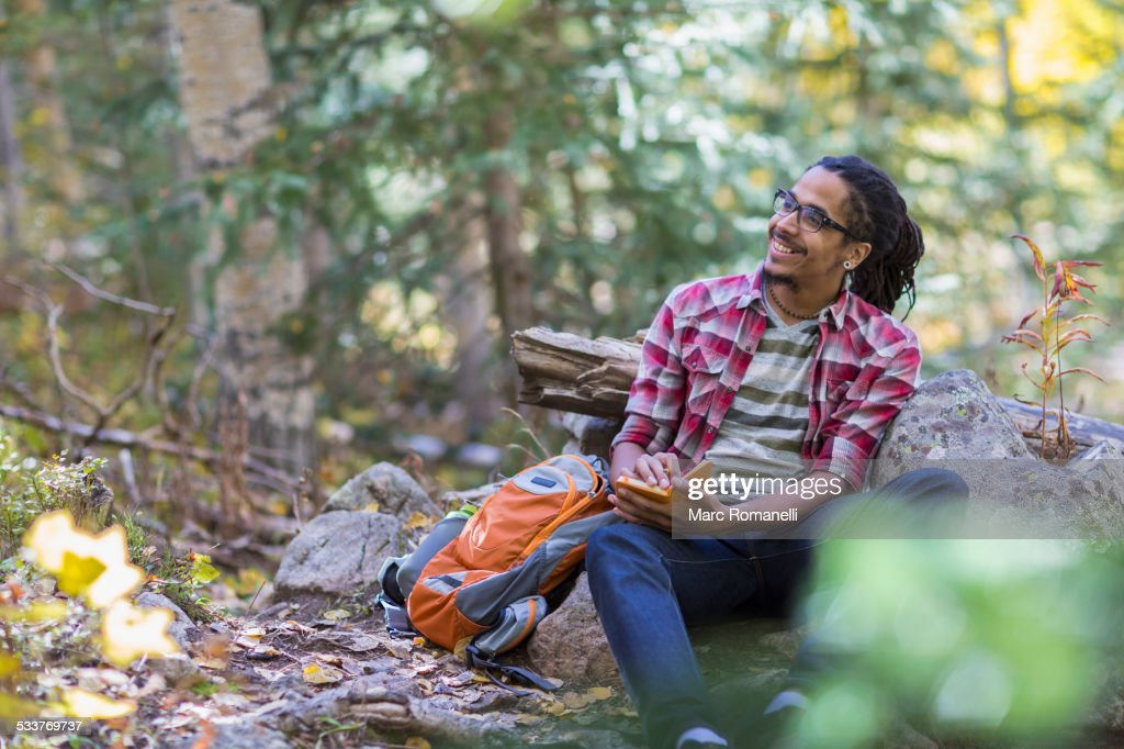 Mixed race hiker writing in forest : Foto stock