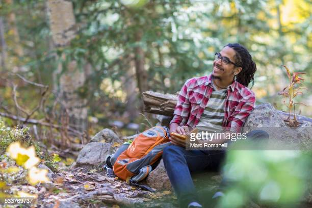Mixed race hiker writing in forest