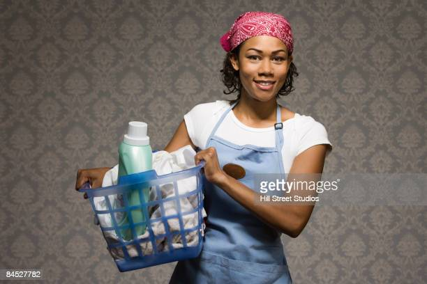 Mixed race housewife carrying laundry in basket