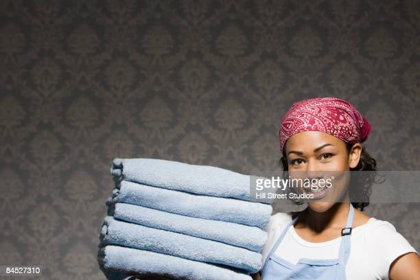 Mixed race housewife carrying stack of folded towels