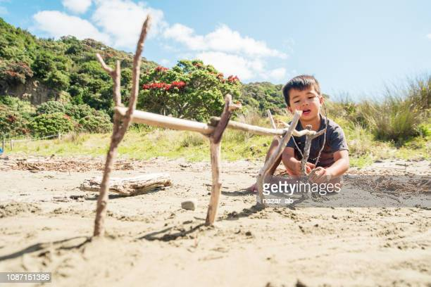 Mixed race kid at beach building with wood.