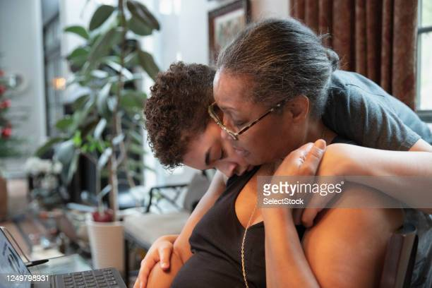 mixed race kid hugging afro american mother - real life stock pictures, royalty-free photos & images