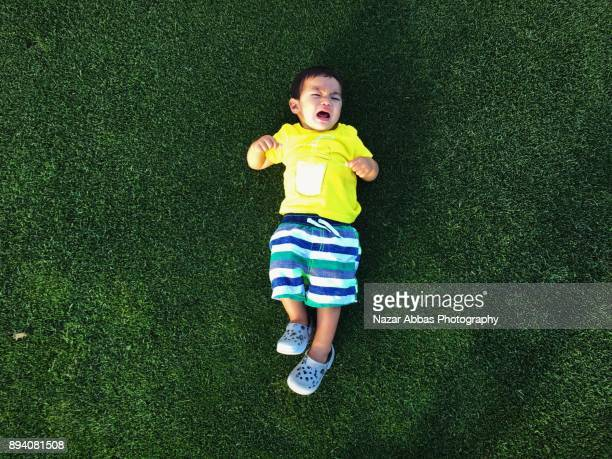 Mixed race Kid lying on green grass and crying.