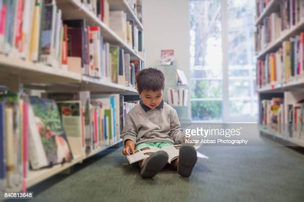 Mixed race kid sitting on library floor and reading book.