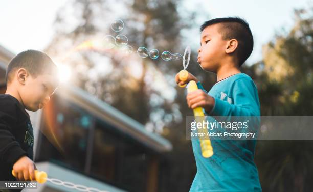 Mixed race kids blowing bubbles.