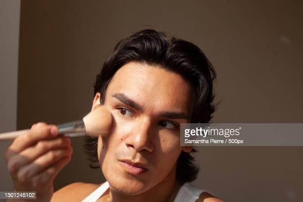 mixed race lgbtq man using makeup,toronto,ontario,canada - applying stock pictures, royalty-free photos & images
