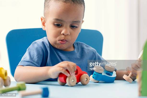 Mixed Race Little boy playing with toy car, eating biscuit.