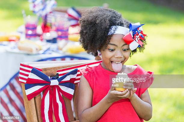 mixed race little girl having cupcake on 4th of july - little girl sticking out tongue stock photos and pictures