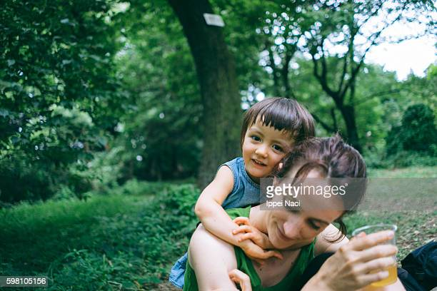 Mixed race little girl hugging her mother from behind in park