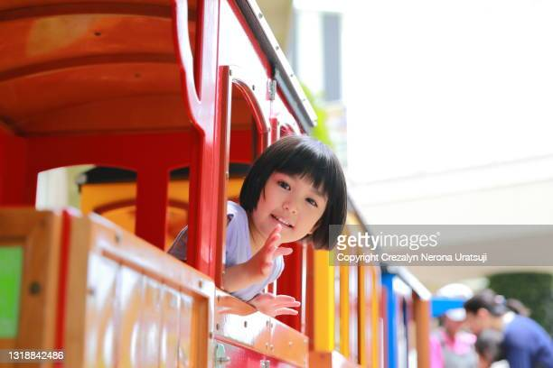 mixed race little girl in a bus mall ride looking at camera waving good bye - saitama prefecture stock pictures, royalty-free photos & images