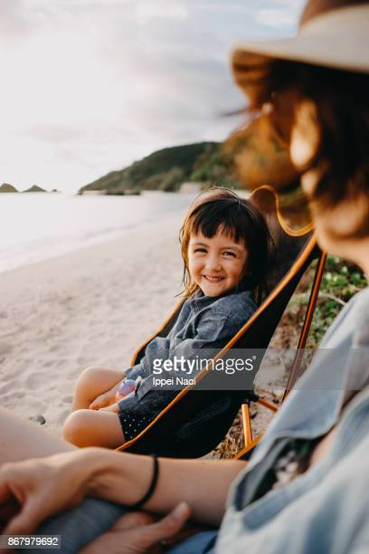 Mixed race little girl smiling at camera on beach at sunset