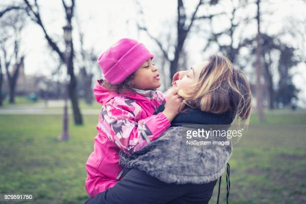Mixed race little girl walking in the park with her Caucasian mother. They are having fun together