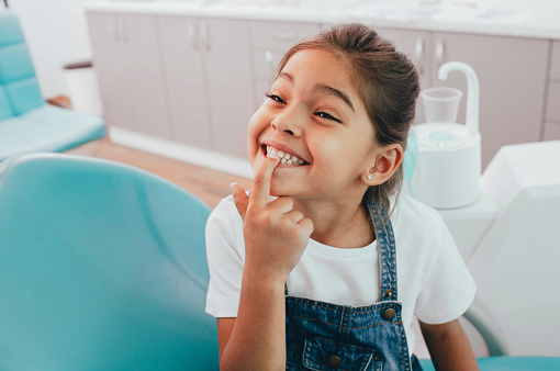 Mixed race little patient showing her perfect toothy smile while sitting dentists chair 1165526820