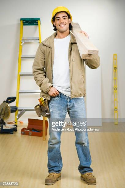 Mixed Race male construction worker carrying wood