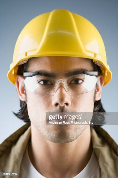 Mixed Race male construction worker wearing hard hat