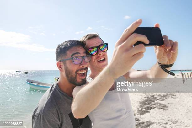 a mixed race, male couple make playful expressions for a selfie on a tropical beach during vacation. - black hair stock pictures, royalty-free photos & images