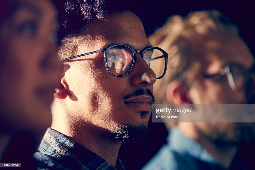 A mixed race male employee watches presentation : Stock Photo