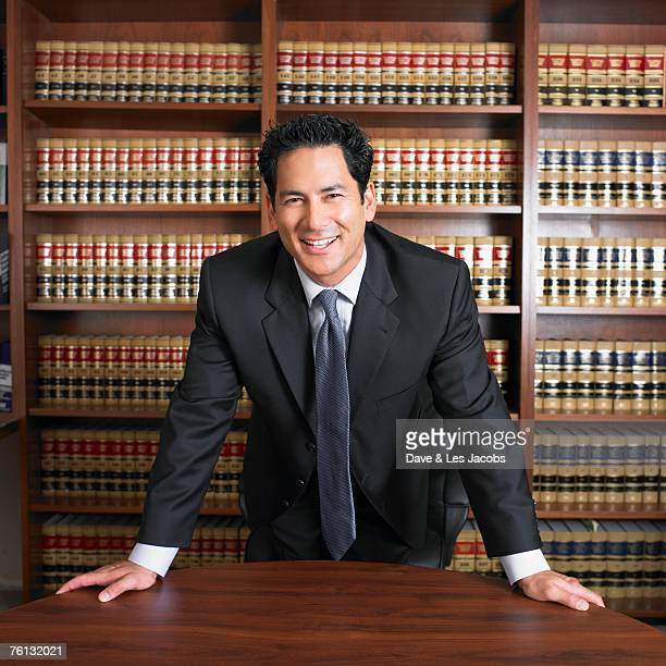 mixed race male lawyer leaning on desk - もたれる ストックフォトと画像