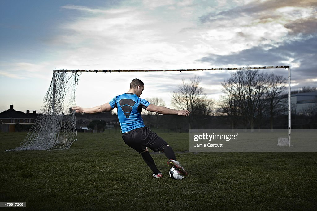 Mixed race male taking a penalty kick : Stock Photo