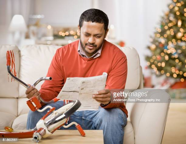 Mixed Race man assembling tricycle on Christmas